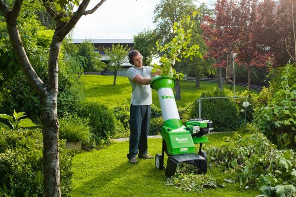 Мужчина использует садовый измельчитель